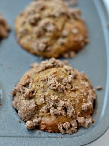 A close up of coffee cake muffin in a muffin tin
