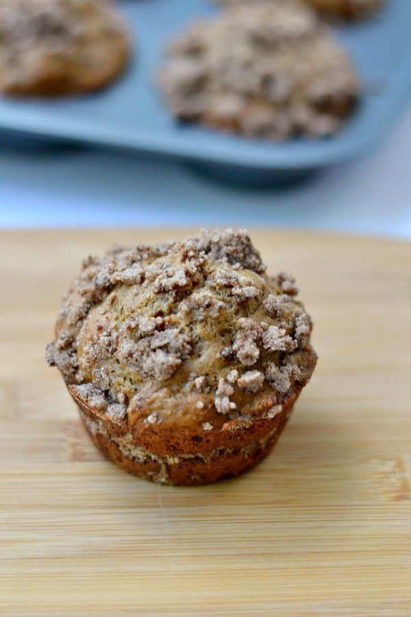 Coffee Cake Muffin on a wood board with muffin tin in background