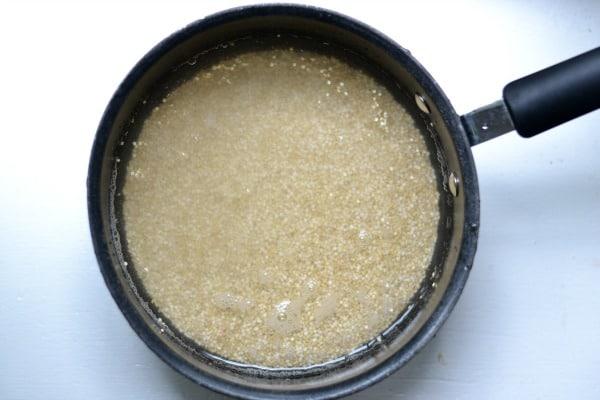 quinoa in a black pot covered in water