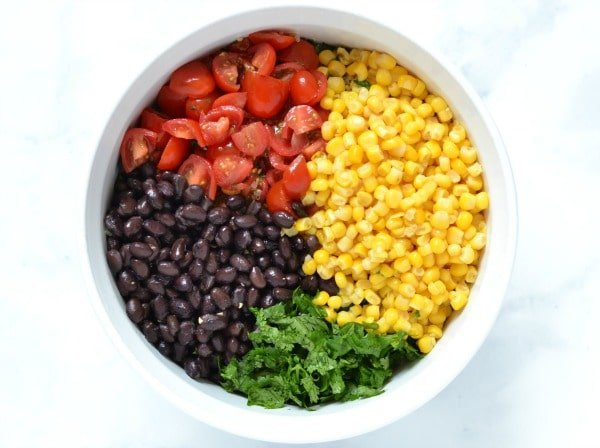 black beans, corn, cilantro, and tomatoes in a white bowl