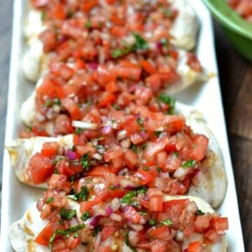 closeup of 5 chicken breasts topped with bruschetta tomato sauce