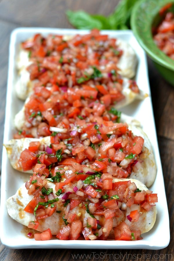 closeup of 5 chicken breasts topped with bruschetta tomatoes
