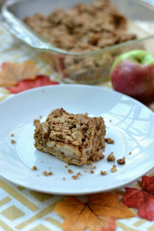 Apple Oatmeal Crumb Bar on a white plate with an apple and dish in the background.