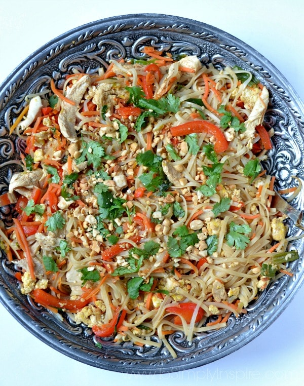 A big silver bowl rice noodles, red pepper strips, cilantro, chicken and peanuts