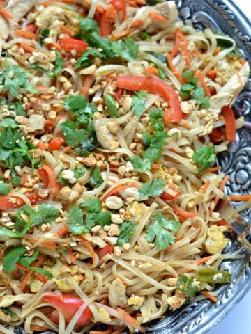 A bowl filled with  Chicken Pad Thai recipe - rice noodles, red pepper strips, cilantro, chicken and peanuts