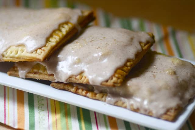 three homemade apple pie pop tarts on a white plate