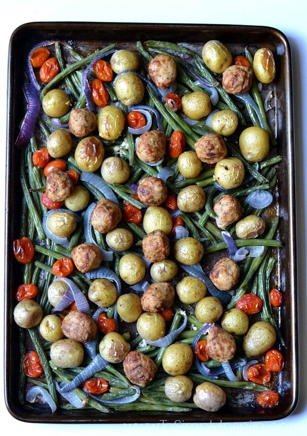 Meatballs with roasted potatoes, green beans and red peppers on a baking sheet.