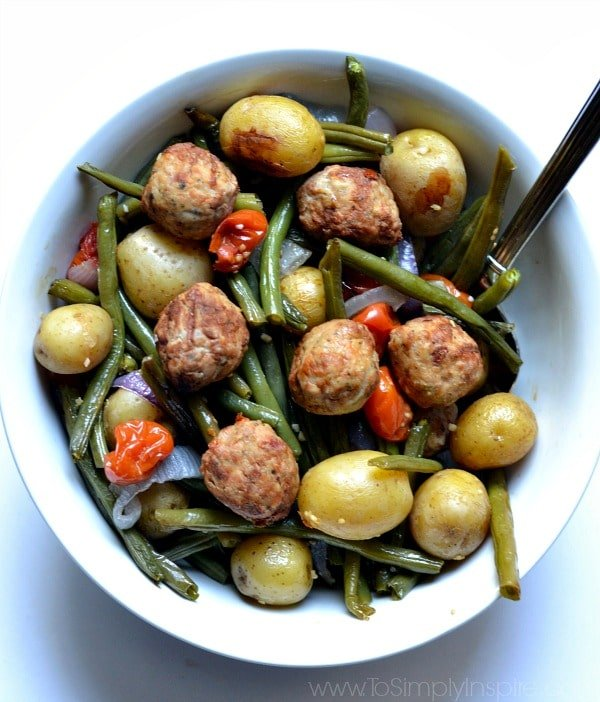 Meatballs with roasted potatoes, green beans and red peppers in a white bowl.