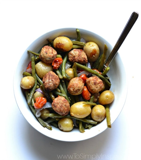 Meatballs with roasted green beans, potatoes and red peppers in a white bowl with a spoon