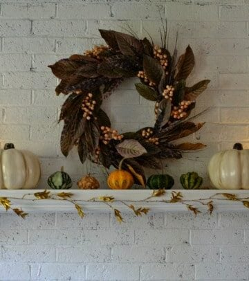 fall leaf wreath on a white mantle with white pumpkins and small pumpkins