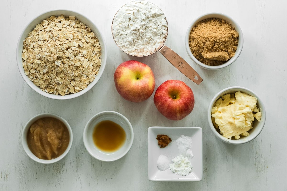 ingredients to make apple oatmeal cookies: two red apples, oatmeal, butter, brown sugar, flour, cinnamon, vanilla extract