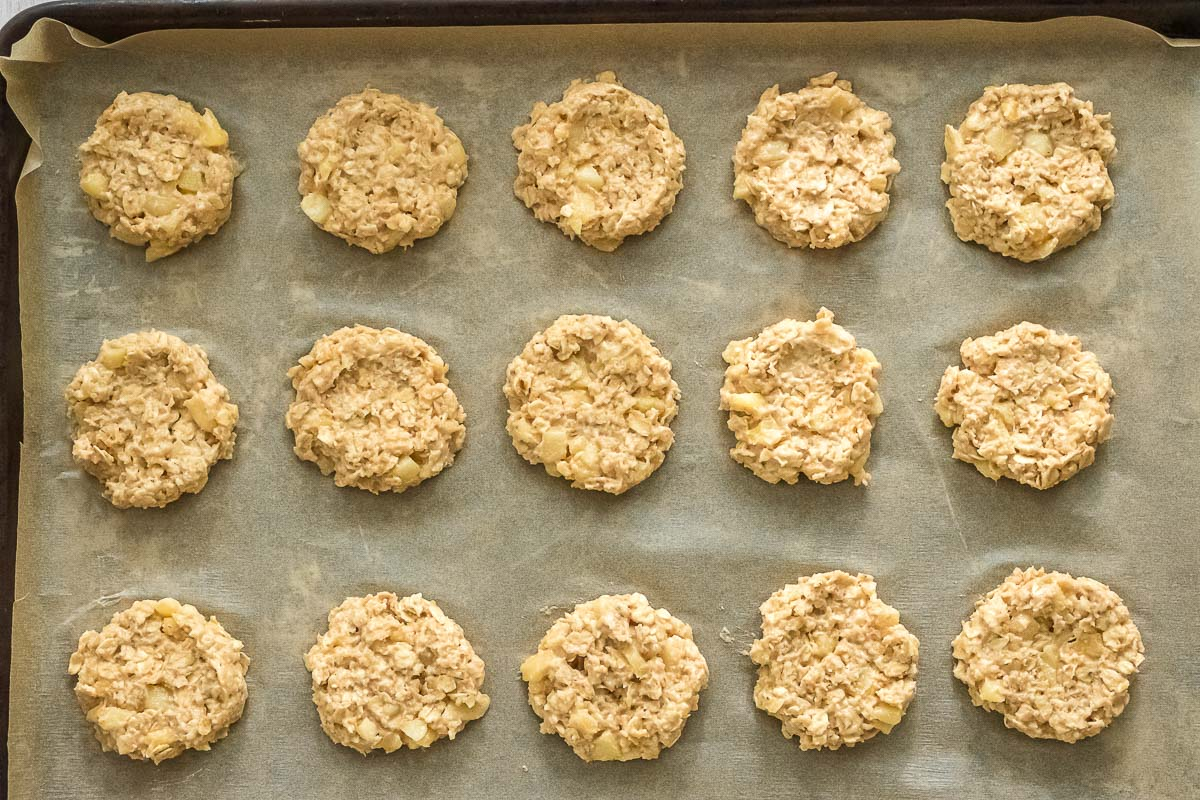 apple oatmeal cookies on a baking sheet lined with parchment paper