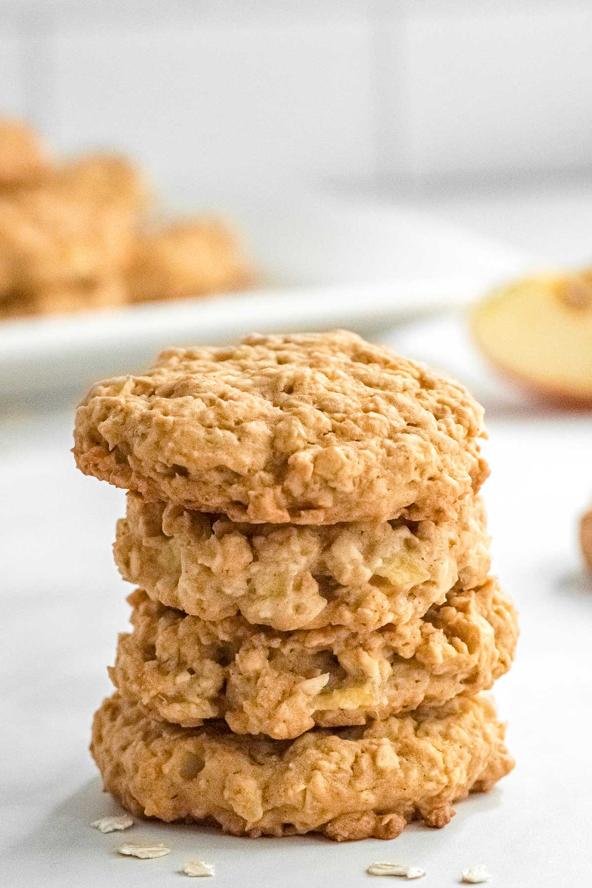 four apple oatmeal cookies stacked with a plateful in the background