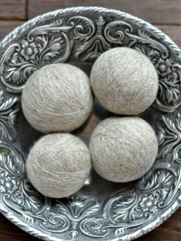 four DIY wool dryer balls in a silver bowl