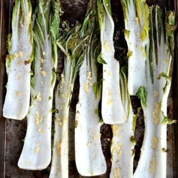 closeup of 8 stalks of Garlic Roasted Bok Choy recipe on a baking sheet