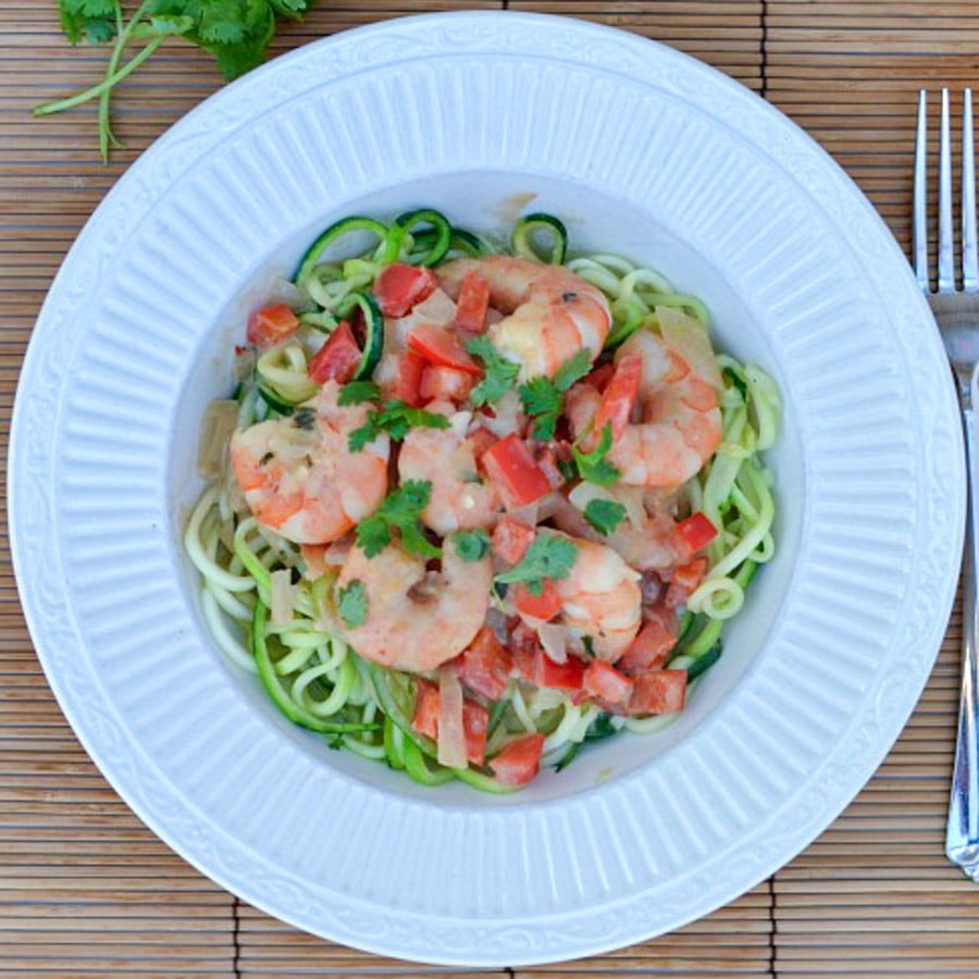 shrimp on top of zucchini noodles in a white bowl
