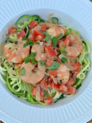 Shrimp Zoodles in Thai Coconut Sauce recipe in a white bowl on a bamboo placemat with text overlay