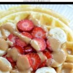 waffle with strawberries and bananas on top with peanut butter drizzle