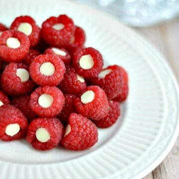 A close up of raspberries with white chocolate chip inside each on a white plate