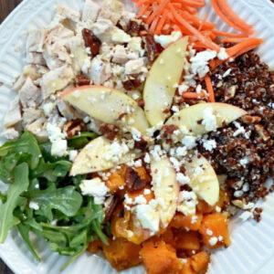 a white bowl fulll of chicken, quinoa, sweet potato, arugula and apple