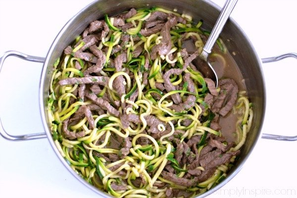 beef teriyaki noodles recipe in a stainless steel pan with spoon