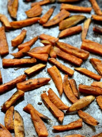 A pile of sweet potato fries on a baking sheet