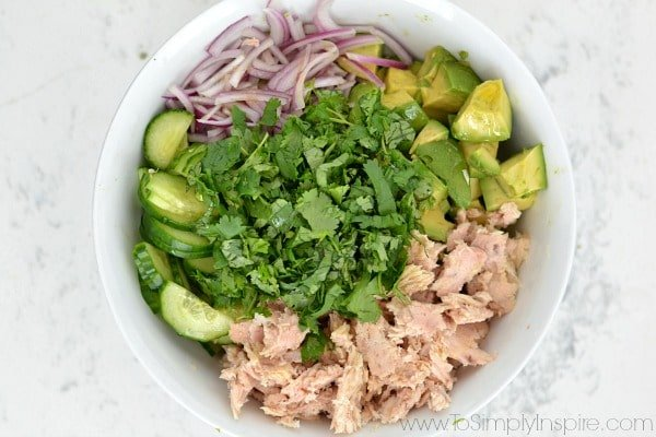 ingredients for avocado tuna salad in separate piles in a big white bowl