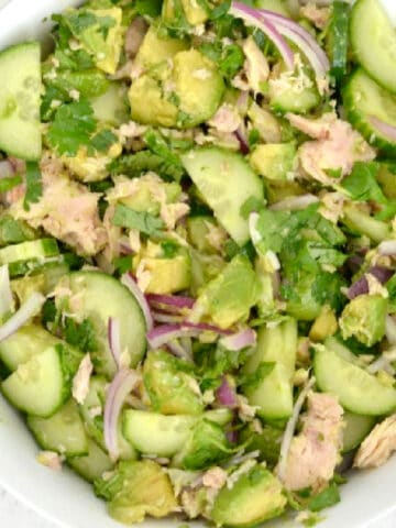 closeup of avocado tuna salad with cucumbers and red onion in a white bowl
