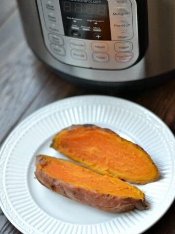 closeup of sweet potato cut open on white plate with an instant pot in background