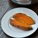 Sweet potato cut open on white plate