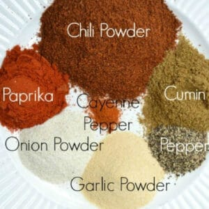 several seasonings in piles on a plate labeled with their names. Chili powder, paprika, cumin, onion powder, garlic powder, pepper and cayenne