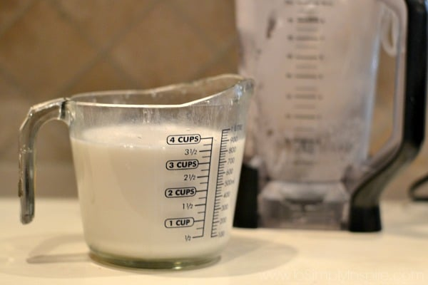homemade coconut milk in a measuring cup with a pitcher in the background