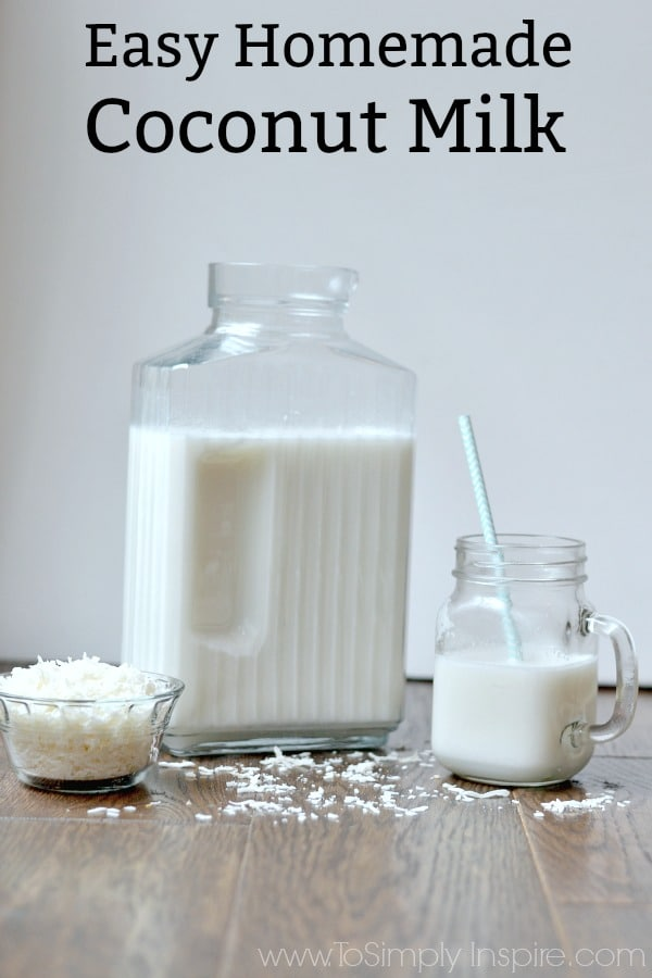 Closeup of homemade coconut milk in a glass with coconut flakes surrounding