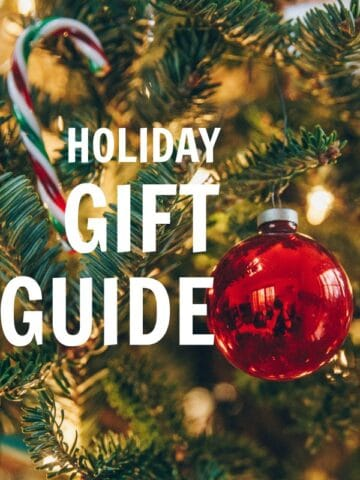 closeup of a red ornament on a christmas tree with text overlay holiday gift guide