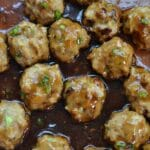 Closeup of a panful Teriyaki Chicken Meatballs Recipe in a brown sauce.