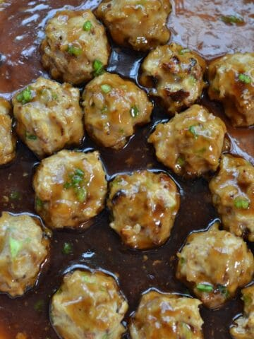 Closeup of a panful Teriyaki Chicken Meatballs Recipe in a brown sauce.