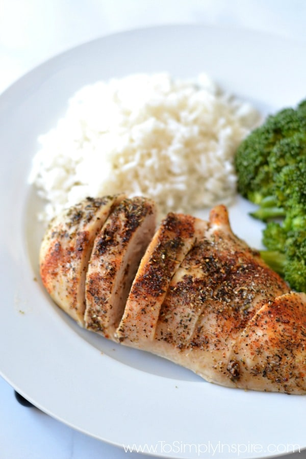 Baked chicken breasts on a white plate with rice and broccoli - recipe at To Simply Inspire