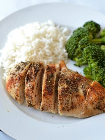 Baked Chicken breast on a white plate with rice and broccoli