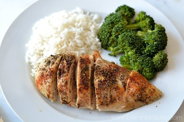 Baked Chicken breast on a white plate with broccoli and rice as side dishes