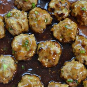 closeup of teriyaki meatballs in brown sauce