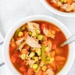 chicken vegetable soup with corn and green beans in a white bowl with a spoon
