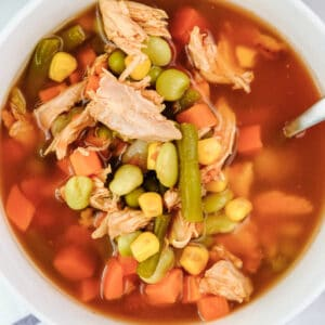 closeup of chicken vegetable soup with carrots, corn and green beans