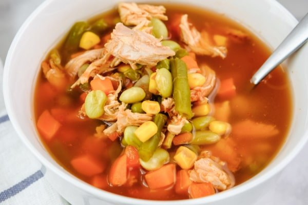 closeup of chicken soup with corn, tomatoes, green peas and green beans