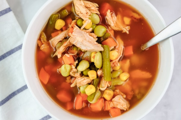 closeup of chicken vegetable soup in a white bowl with a spoon