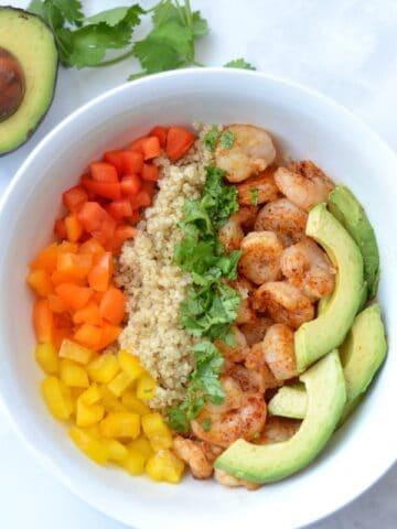 closeup of a bowl of Shrimp, quinoa, sliced avocado and red, yellow, orange peppers