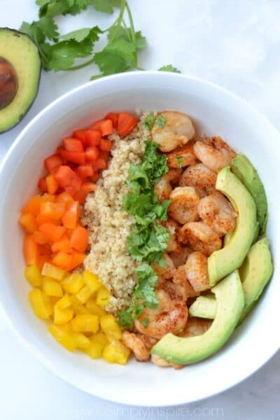 closeup of Shrimp, quinoa, sliced avocado and red, yellow, orange peppers