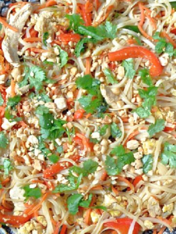 homemade chicken pad thai in a silver bowl topped with peanuts and cilantro pieces