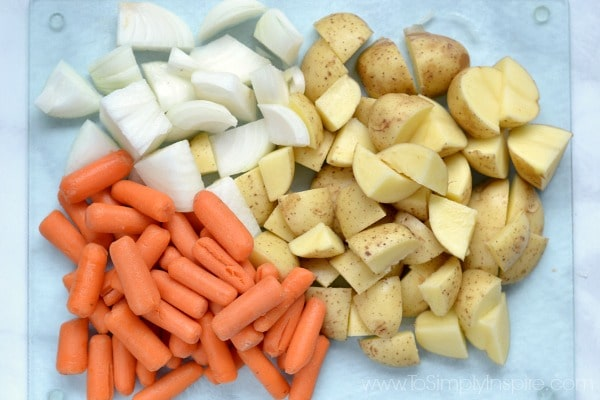 diced potatoes, carrots and onions on a glass cutting board