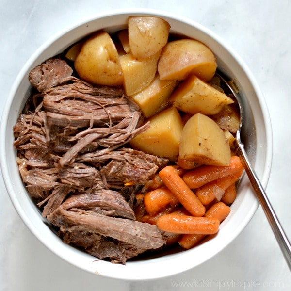 A white bowl is filled with Pot Roast and Gravy