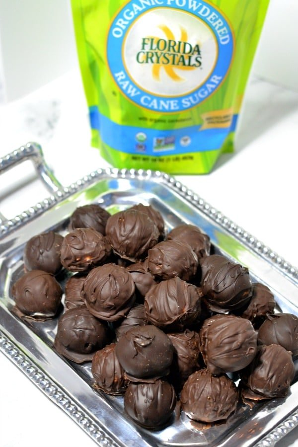 peanut butter balls on a silver stray with a package of Florida crystal powdered sugar